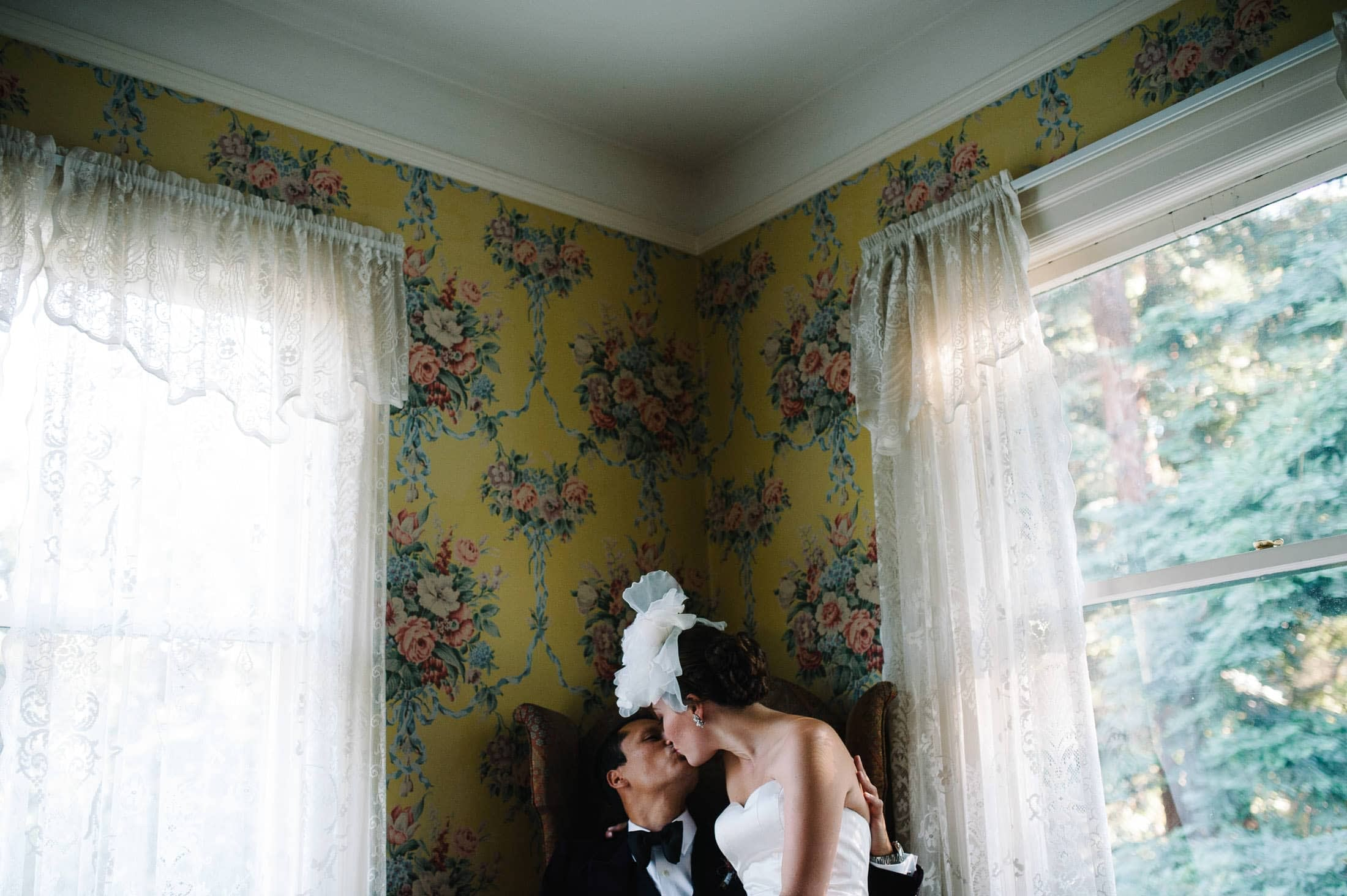 fun artistic shot of bride and groom kissing against floral wall paper at Atherton Wedding