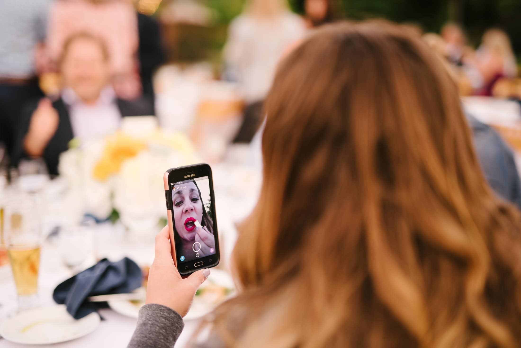 Great Pic of woman putting on lipstick at wedding
