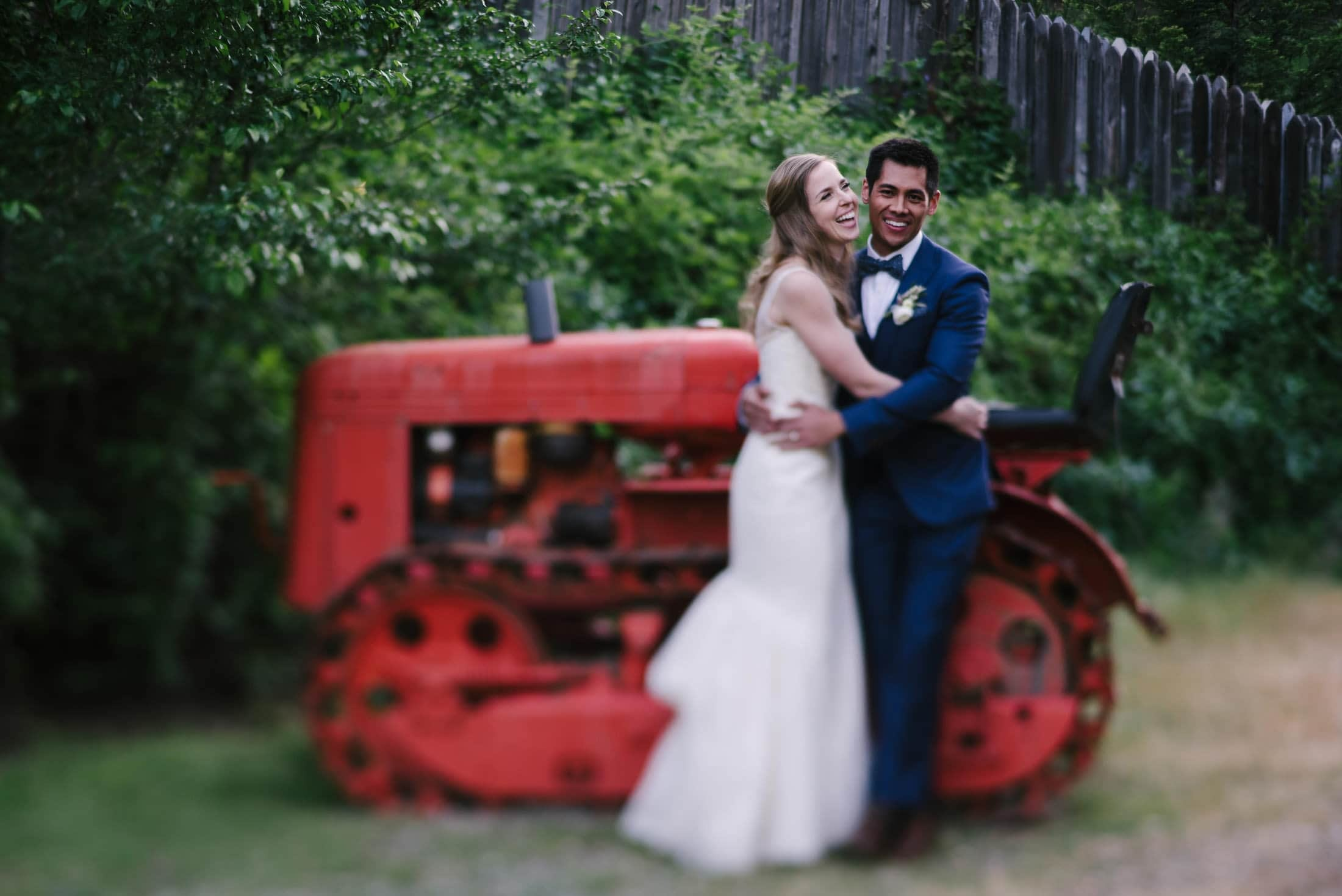 couple laughing on tractor at radonich ranch wedding