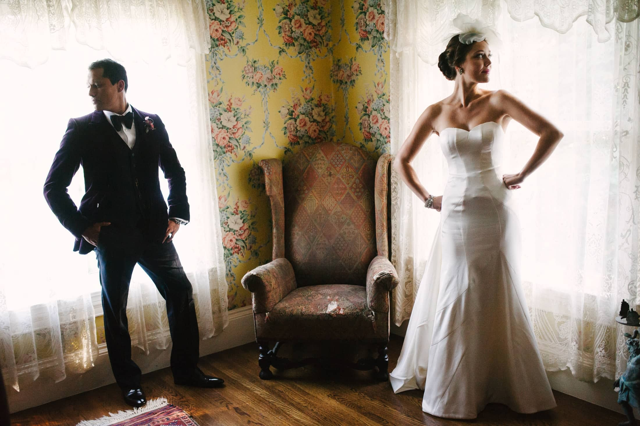 fun artistic shot of bride and groom against floral wall paper at Atherton Wedding