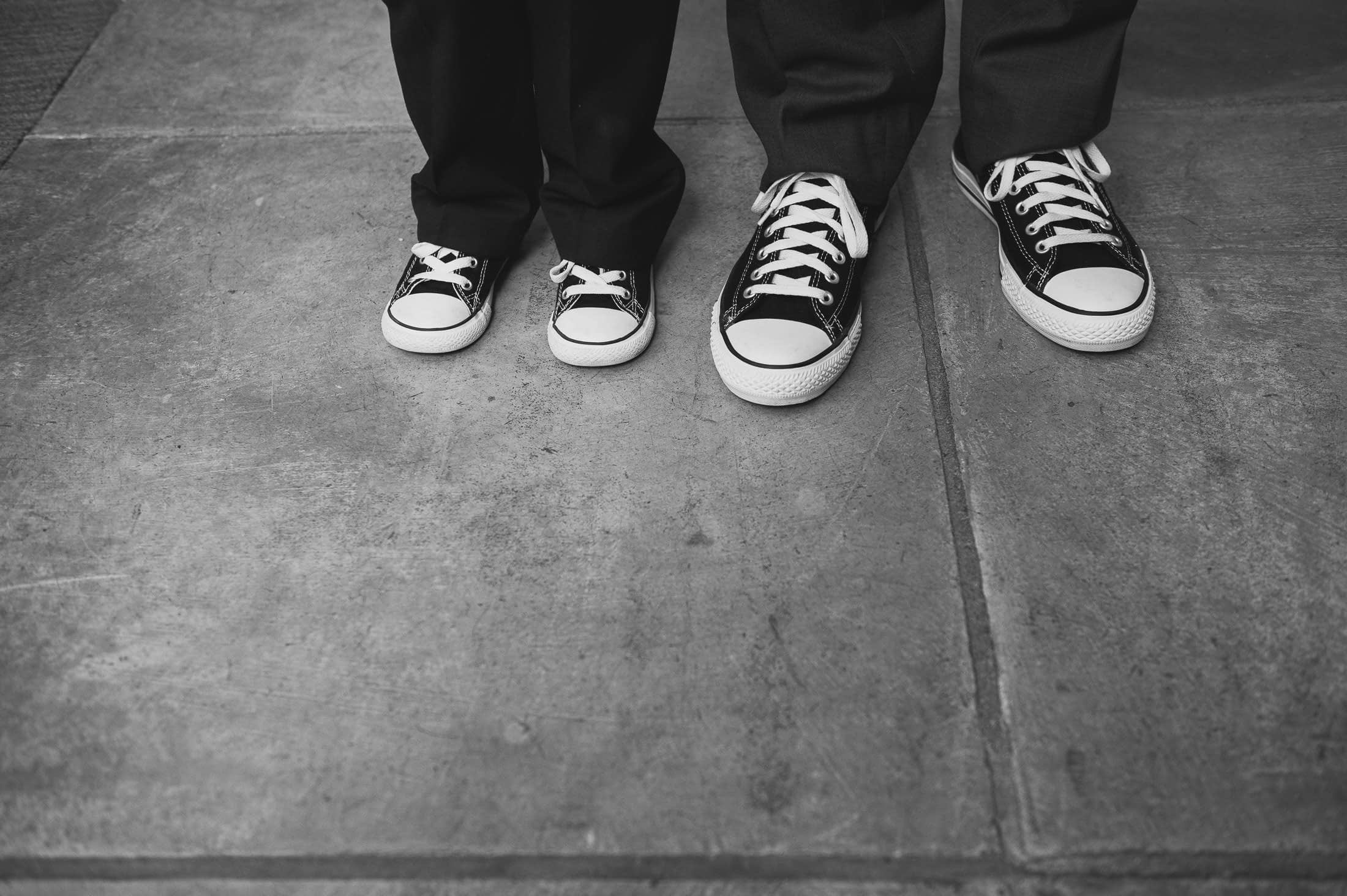 Artistic wedding detail of adult and kid wearing converse
